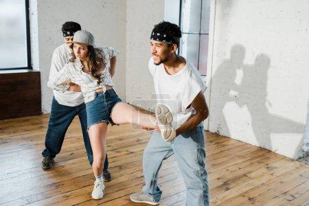 heureux afro-américain danseur tenant jambe de fille en studio de danse