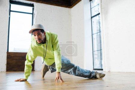 Photo pour Bel homme afro-américain en casquette breakdance en studio de danse - image libre de droit