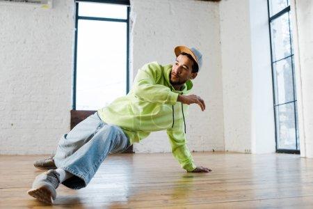 stylish african american man in cap breakdancing in dance studio