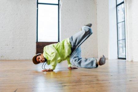 hombre afroamericano de moda en breakdance de gorra en estudio de baile