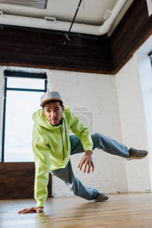 stylish and young african american man in cap breakdancing in dance studio