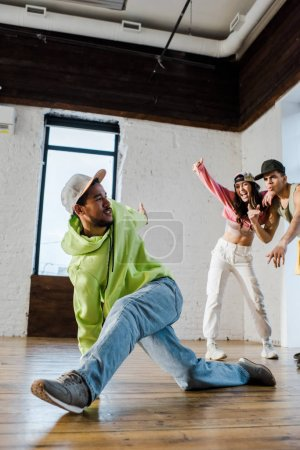 selective focus of african american dancer breakdancing near emotional man and girl