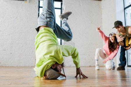 Photo pour Foyer sélectif du danseur afro-américain breakdance près de l'homme et la femme émotionnelle - image libre de droit