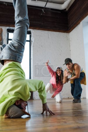 Photo for Selective focus of emotional dancers looking at african american man breakdancing in dance studio - Royalty Free Image