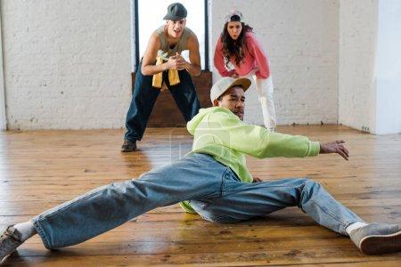 Photo pour Foyer sélectif de bel homme afro-américain breakdance près de danseurs émotionnels - image libre de droit