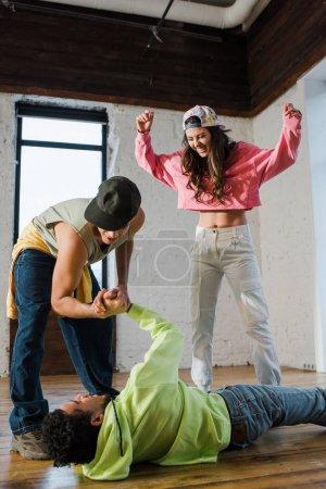 excitada chica sonriendo cerca de bailarines multiculturales tomados de la mano en el estudio de baile
