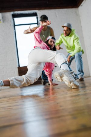 Photo for Selective focus of girl breakdancing near emotional multicultural men - Royalty Free Image