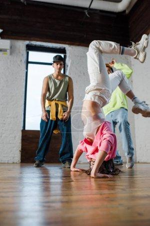 enfoque selectivo de chica haciendo handstand mientras breakdance cerca de los hombres multiculturales