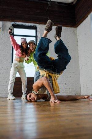 enfoque selectivo de hombre guapo breakdancing cerca de bailarines multiculturales emocionados