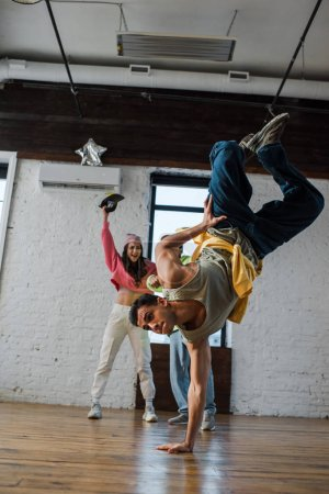 Photo for Selective focus of man breakdancing near excited multicultural dancers - Royalty Free Image