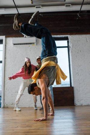 Photo pour Foyer sélectif de l'homme faisant handstand tandis que breakdance près de danseurs multiculturels - image libre de droit