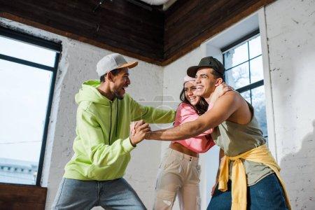 Aufgeregte multikulturelle Tänzer halten Händchen nahe glücklicher Frau