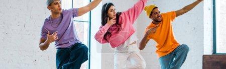 plan panoramique de jeune femme et hommes multiculturels élégants breakdance