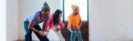 plan panoramique de la femme et élégant multiculturel hommes breakdance