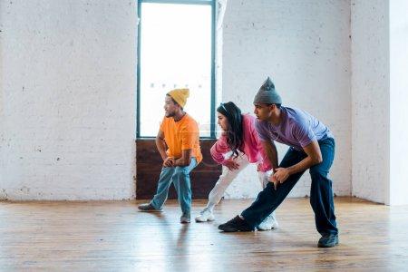 jeune femme et hommes multiculturels élégants étirant dans le studio de danse