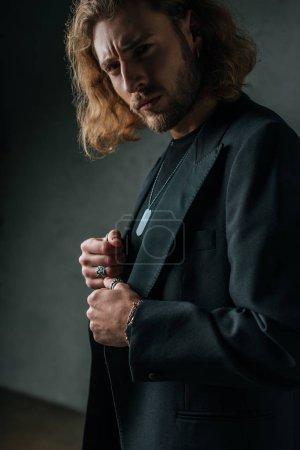 Photo pour Homme d'affaires à la mode tendu en costume noir posant dans l'obscurité - image libre de droit