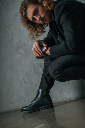 Photo for Tense fashionable businessman in black suit posing in dark near grey wall - Royalty Free Image