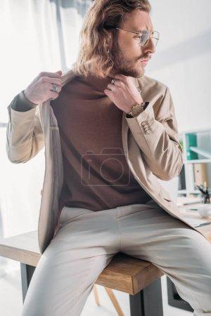Photo pour Vue à angle bas de l'homme d'affaires élégant à la mode assis sur le bureau et posant dans le bureau - image libre de droit