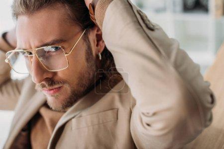 Photo pour Vue rapprochée de l'homme d'affaires à la mode en lunettes posant avec les mains derrière la tête - image libre de droit