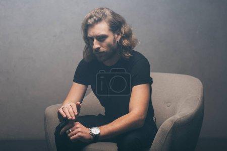 Photo pour Homme d'affaires à la mode en tenue noire assis dans un fauteuil avec plus léger près du mur gris - image libre de droit