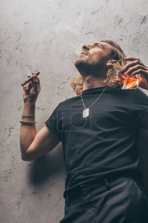 Photo for Low angle view of fashionable businessman in black outfit smoking cigar and drinking whiskey near grey wall - Royalty Free Image