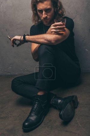 Photo pour Homme d'affaires à la mode en tenue noire assis sur le sol avec cigare et whisky près du mur gris - image libre de droit