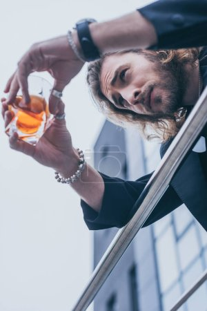 Photo for Low angle view of fashionable businessman in black suit holding glass of whiskey near office building and railing - Royalty Free Image