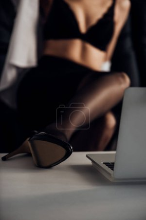 Cropped view of attractive girl in stockings and high heeled shoe posing in front of web camera