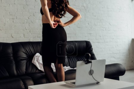 Photo for Cropped view of sexy woman taking off skirt in front of laptop with web camera - Royalty Free Image