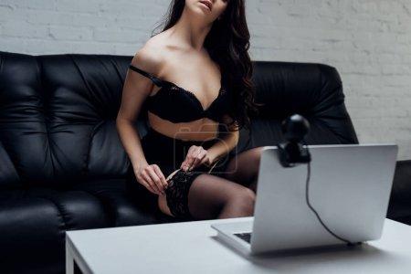 Photo pour Vue recadrée de femme sexy en jupe et soutien-gorge décoller bas devant sur ordinateur portable avec caméra web - image libre de droit
