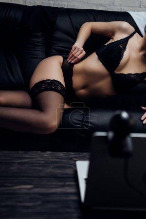 Photo pour Vue recadrée de belle femme en lingerie posant à la caméra web sur le canapé - image libre de droit