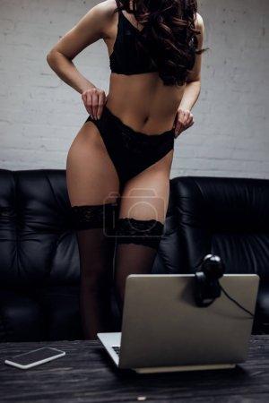 Photo pour Vue recadrée de femme sexy en lingerie noire et bas posant devant sur la caméra web - image libre de droit