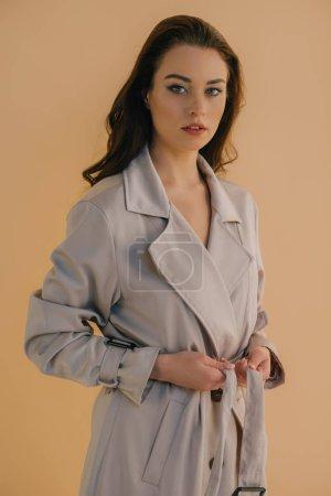 Photo pour Jolie jeune femme en manteau regardant la caméra isolée sur beige - image libre de droit