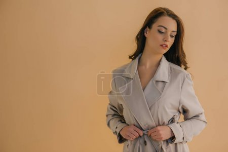 schöne junge Frau in Mantel isoliert auf beige mit Kopierraum