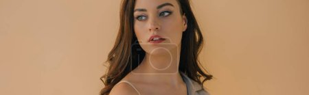 Photo for Panoramic shot of beautiful girl in bra and coat looking away isolated on beige - Royalty Free Image