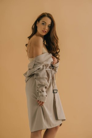 Photo for Side view of sensual woman in bra and coat looking at camera isolated on beige - Royalty Free Image