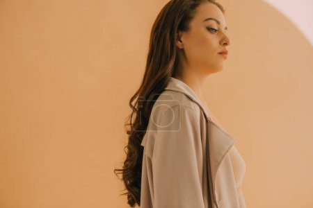 Photo for Side view of attractive girl in coat and bra on beige background - Royalty Free Image