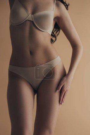 Foto de Vista cruzada de la sexy mujer en sujetador y los pechos con la mano en cadera aislada en beige. - Imagen libre de derechos