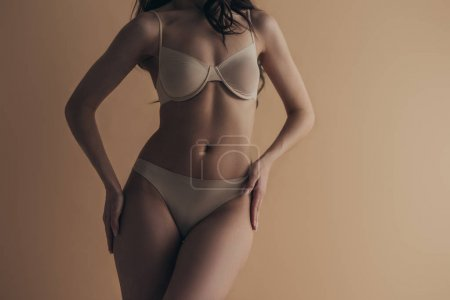 Photo for Cropped view of sensual girl in underwear with hands on hips isolated on beige - Royalty Free Image