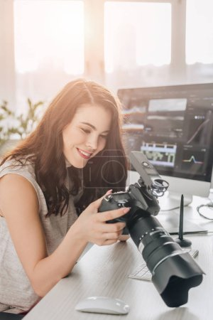 Photo for Happy art editor holding digital camera near computer monitor - Royalty Free Image