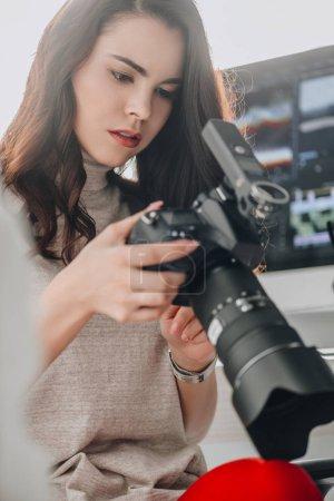 Photo pour Focus sélectif d'un éditeur artistique attirant tenant un appareil photo numérique près d'un écran d'ordinateur - image libre de droit