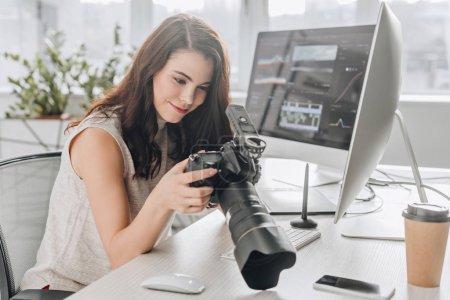 Photo pour Heureux éditeur d'art tenant appareil photo numérique près des moniteurs d'ordinateur - image libre de droit