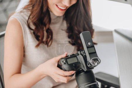 Photo pour Crochet d'un monteur artistique heureux tenant un appareil photo numérique - image libre de droit