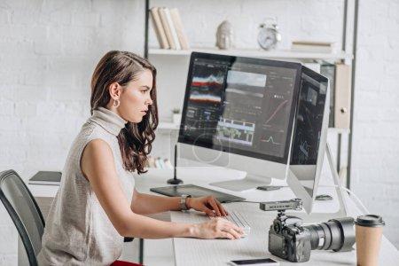 Photo pour Vue latérale de l'éditeur d'art attrayant travaillant près des moniteurs d'ordinateur - image libre de droit