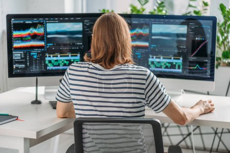 Photo for Back view of editor working near computer monitors - Royalty Free Image
