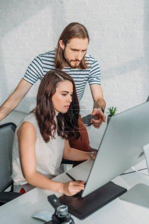 Photo pour Barbe d'une rédactrice artistique pointant du doigt vers un écran d'ordinateur - image libre de droit