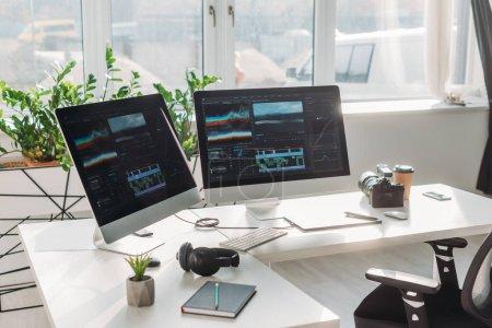 Photo pour Moniteurs d'ordinateur avec storyboard près des écouteurs et tasse en papier sur la table - image libre de droit