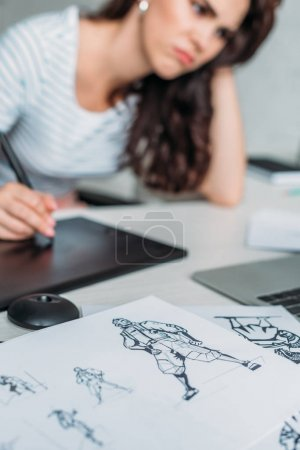 Photo for Selective focus of cartoon sketches near displeased animator using digital tablet - Royalty Free Image