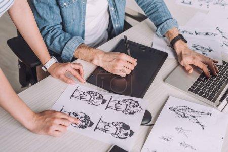 Photo pour Vue en coupe d'un illustrateur pointant du doigt sur un dessin animé près d'un collègue - image libre de droit
