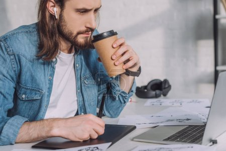 Photo for Bearded of animator in wireless earphones holding paper cup - Royalty Free Image